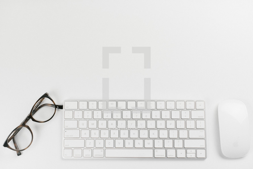 Mouse, keyboard, and glasses on a white desk