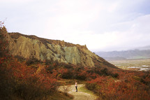 a woman walking on a dirt path surrounded by cliffs