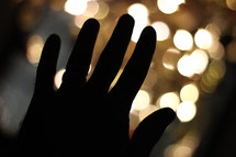 Silhouette of a hand in front of lights.