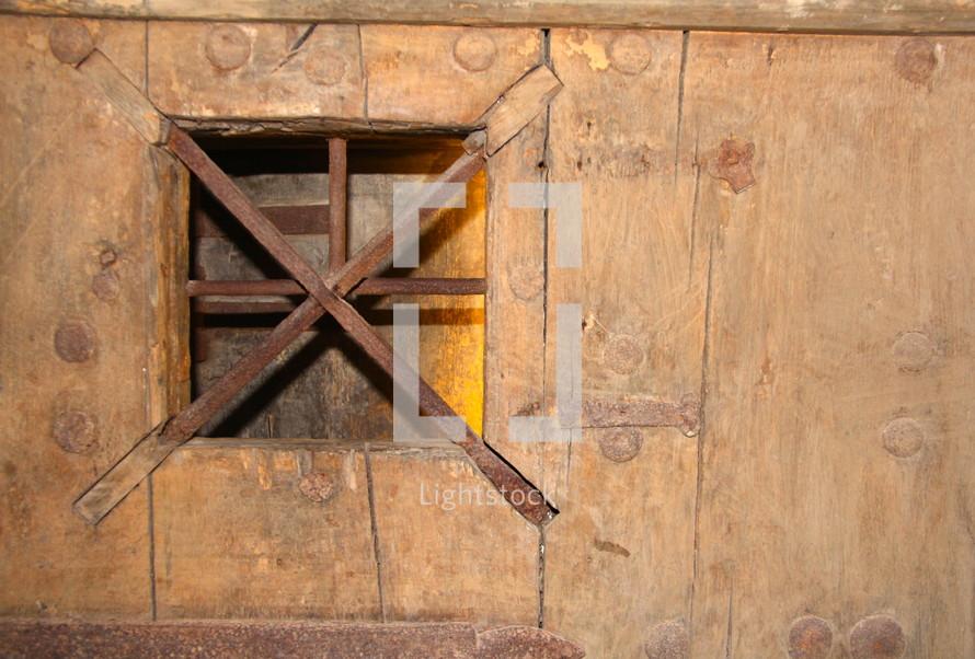 barred window on a wood door