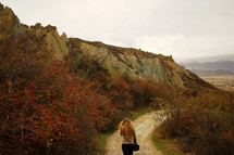 a woman walking down a dirt road