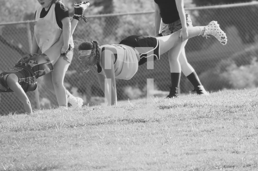 teens girls doing a wheelbarrow race