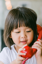 little girl talking on a red telephone