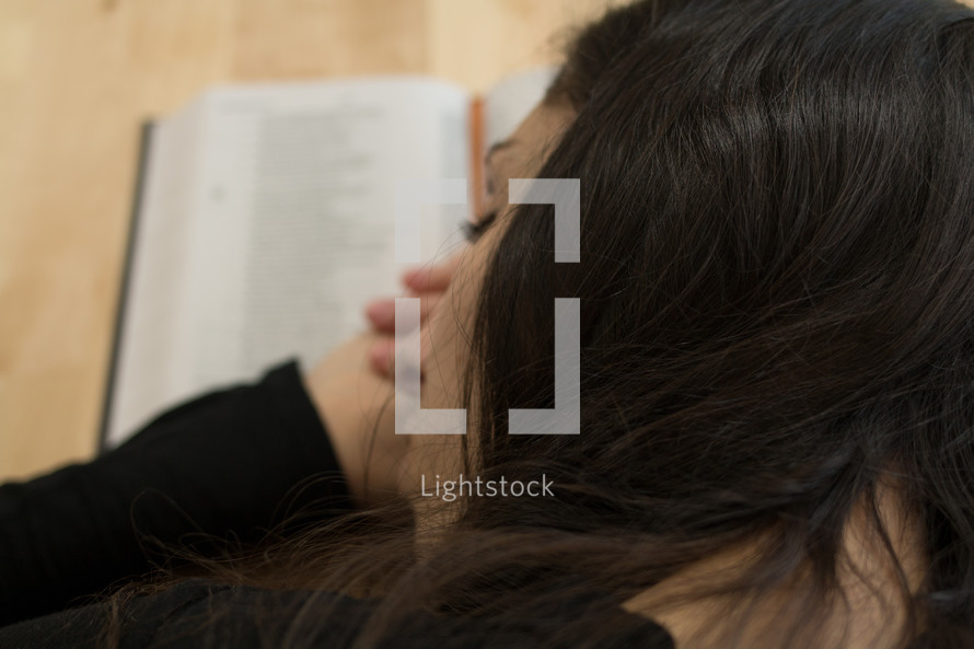 a woman sleeping on an open book