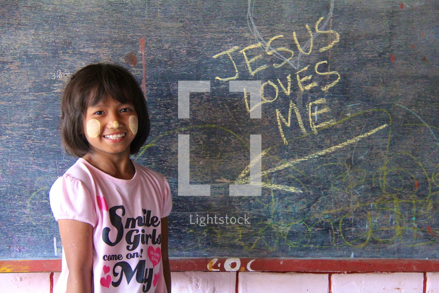 Jesus loves me on a chalkboard pointing to you a young girl in Myanmar