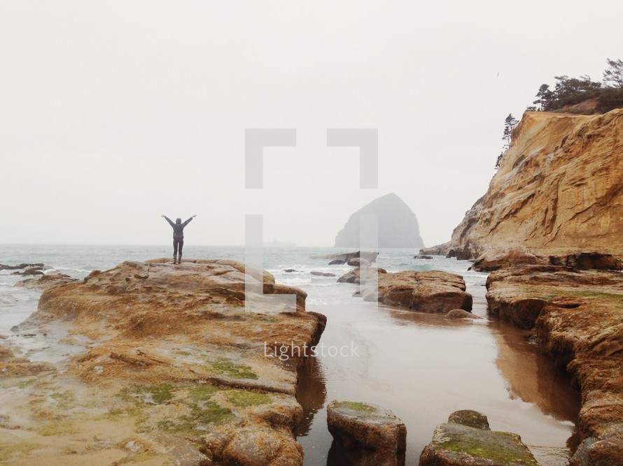 a man with arms raised standing on a rocky shore