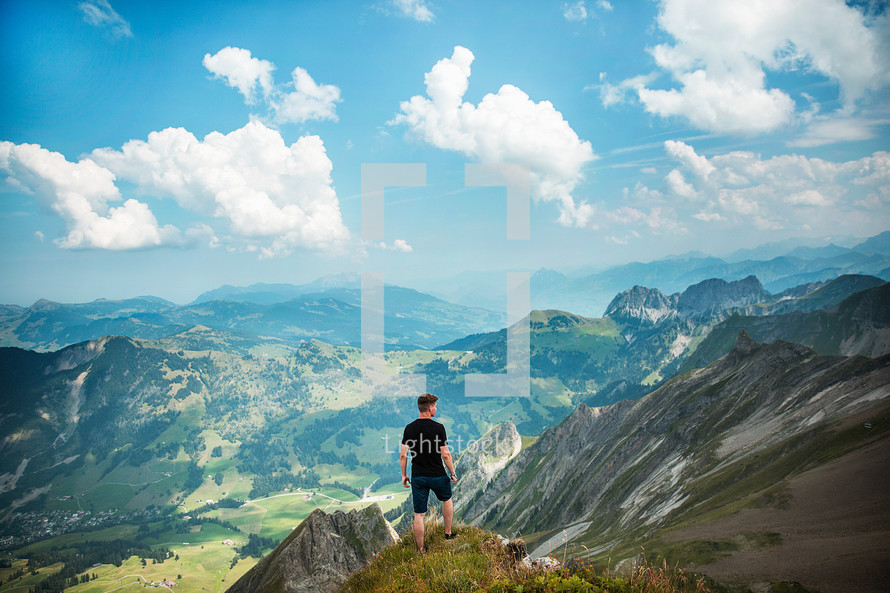 man standing at the edge of a cliff looking out over a valley