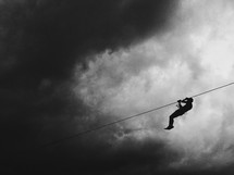 Zip lining under stormy clouds.