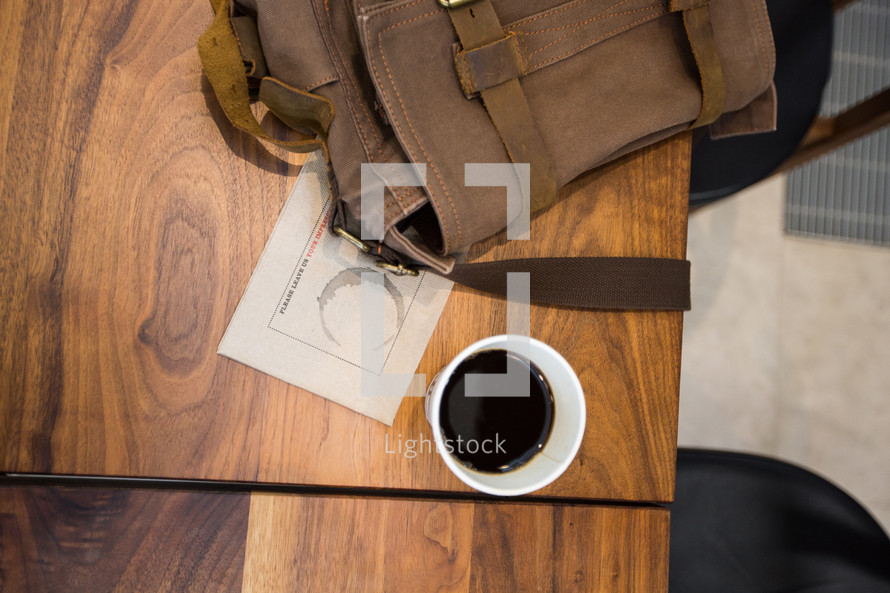 coffee cup and backpack on a wood table