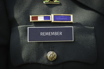 """The word """"remember"""" printed on the military name badge of uniform."""