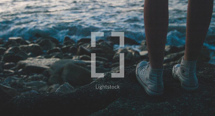 woman's feet in sneakers on rocky
