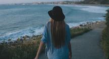 woman walking on a path at a beach