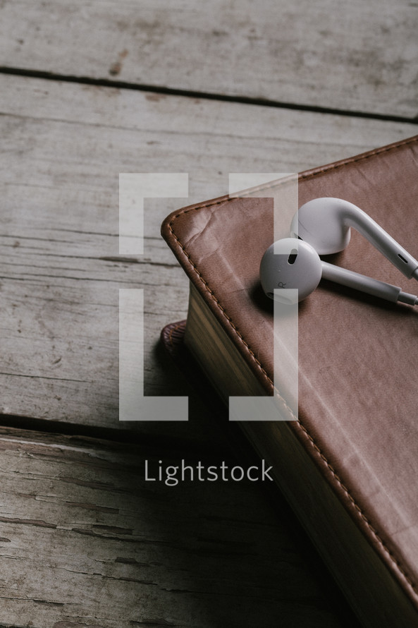 Ear buds on top of closed Bible laying on top of wooden table.