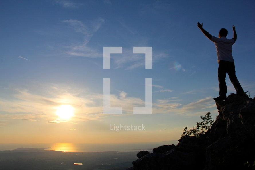 man standing on a mountain top looking out with raised hands  to God  with rising / setting sun in the background