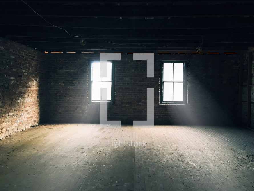 rays of sunlight pouring through windows into an empty room