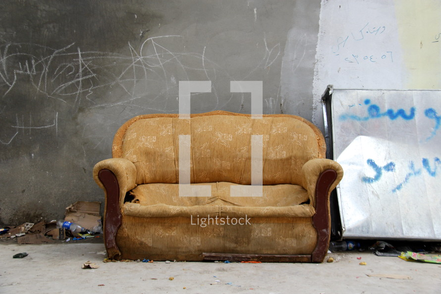 old couch and a graffiti covered wall in a refugee camp in Erbil, Iraq