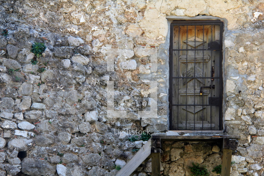 barred door and stone wall