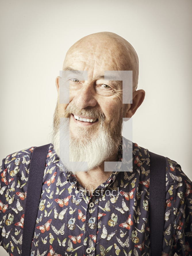 an elderly man in suspenders smiling