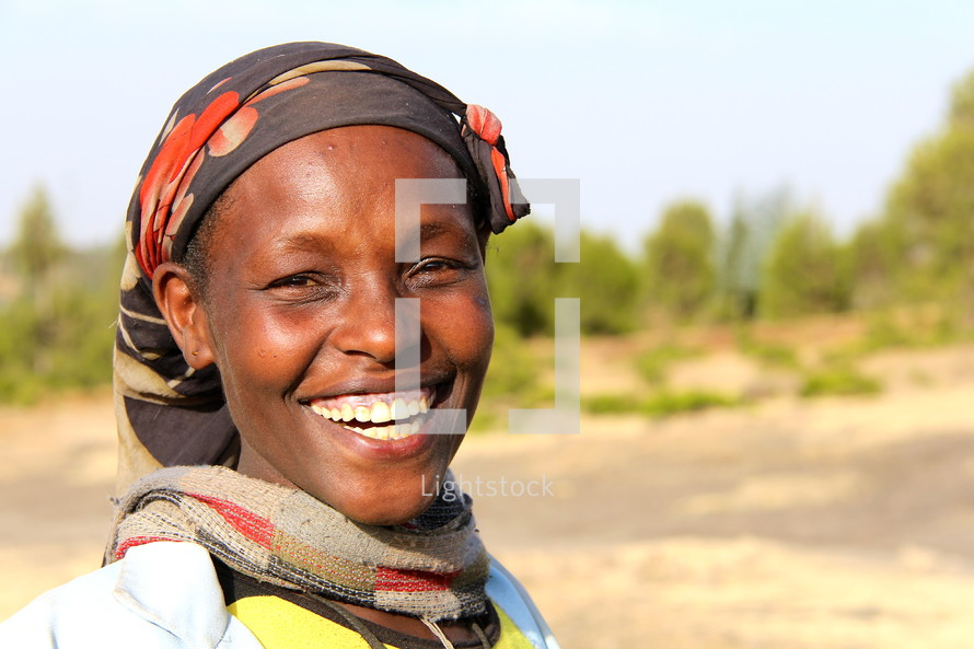 African woman with a huge smile wearing a traditional head scarf