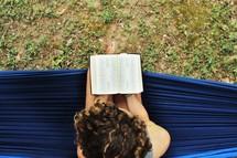 a woman reading a Bible on a hammock