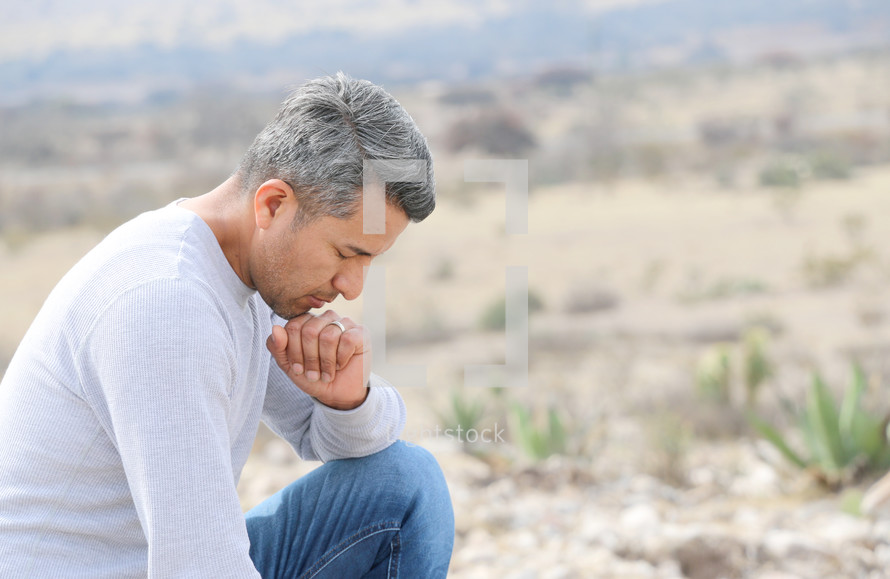 a man kneeling in prayer in a desert