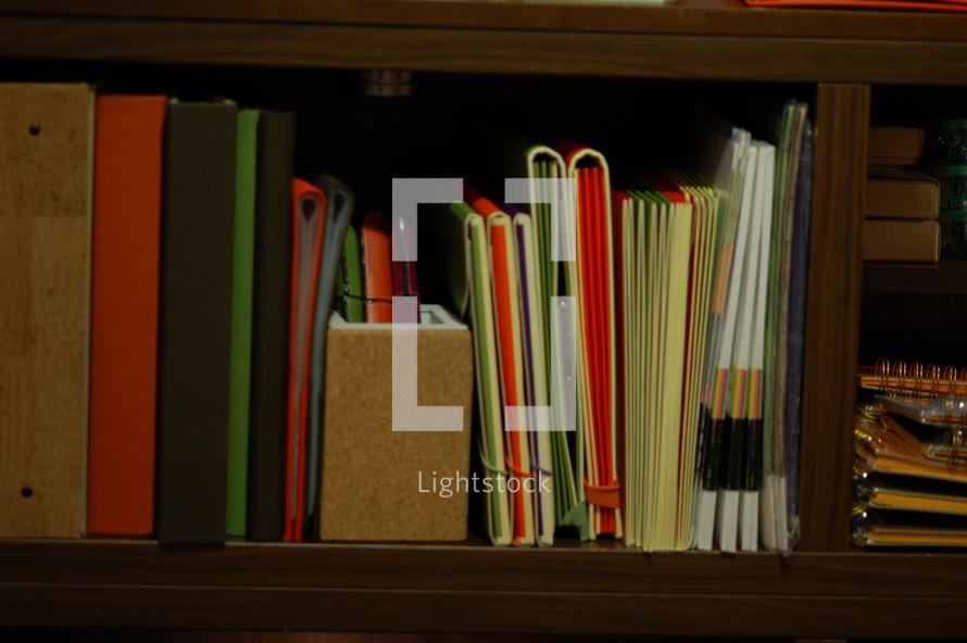 Bookshelf with books and binders.