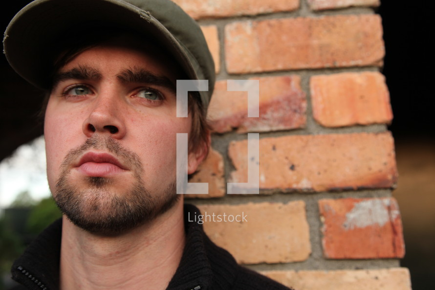 pouting face of a man with a beard, mustache, cap, bushy eyebrows, brick wall