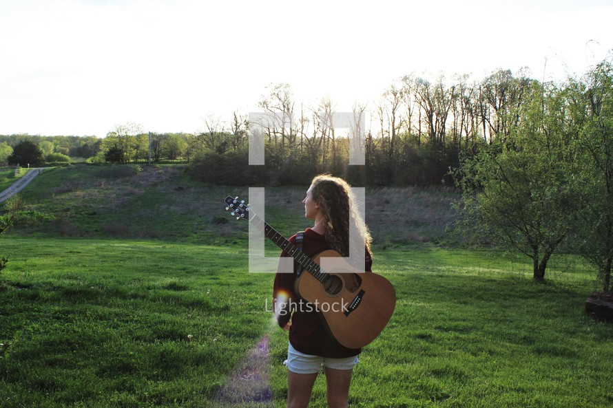 a girl with a guitar on a her back walking outdoors