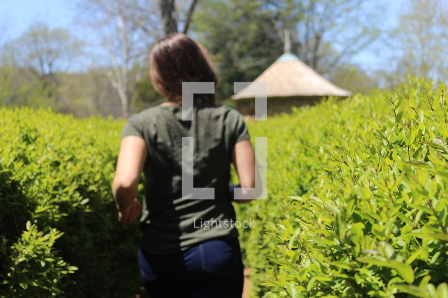 a girl walking outdoors through blueberry bushes