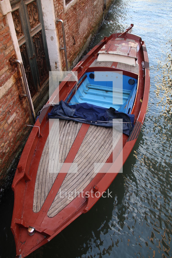 boat docked against a brick wall of a building