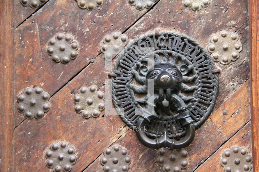 Lion door knocker on ancient wooden door