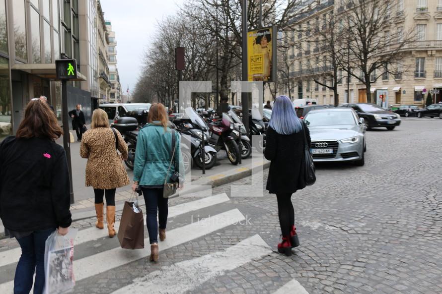 women walking across a crosswalk
