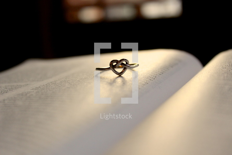 Heart knot ring on page of open Bible.