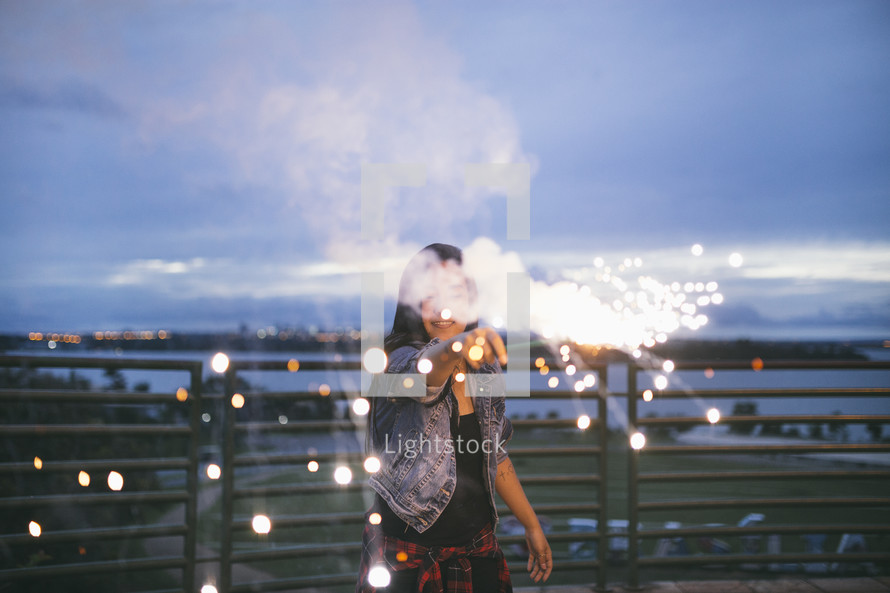 woman holding a sparkler under a cloudy sky