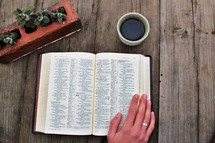 man's hand on the pages of a Bible