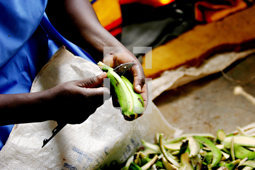 African woman peeling  fruit plantain knife cooking