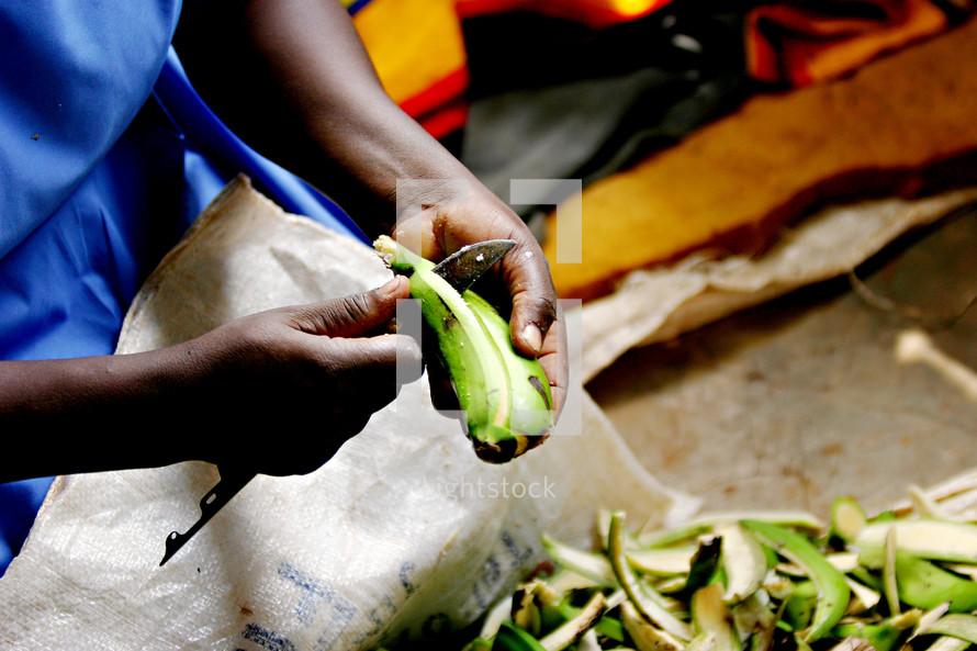African woman peeling  fruit plantain knife cooking