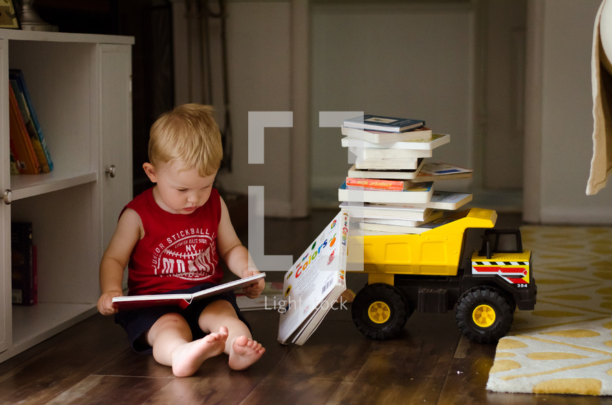 a toddler boy sitting and reading books next to a toy dump truck