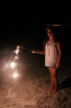 A little girl holding a sparkler on a beach