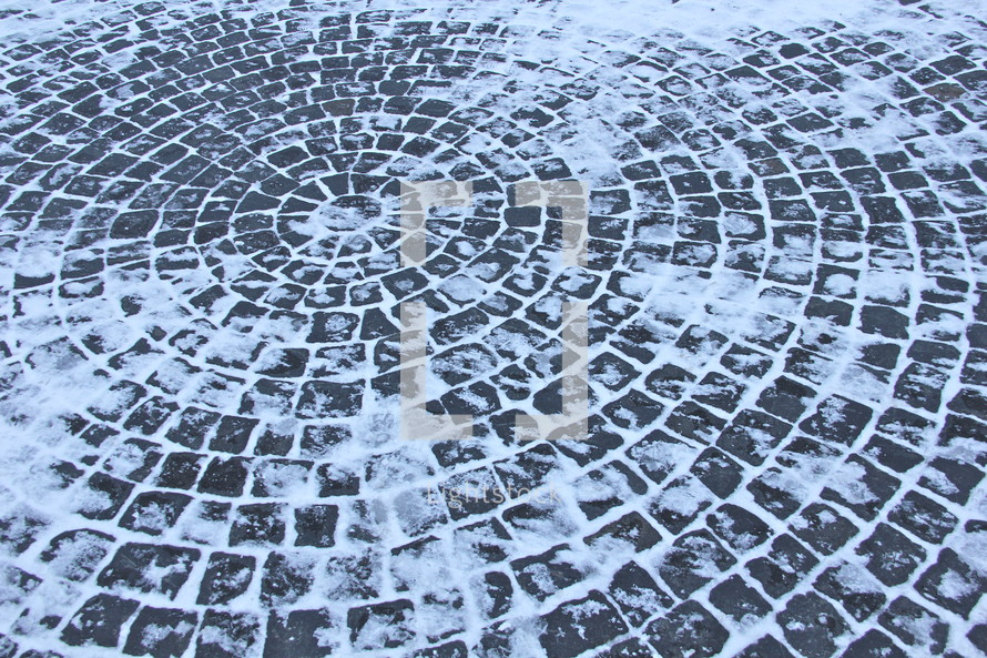 Snow and Ice-covered circular stone path.