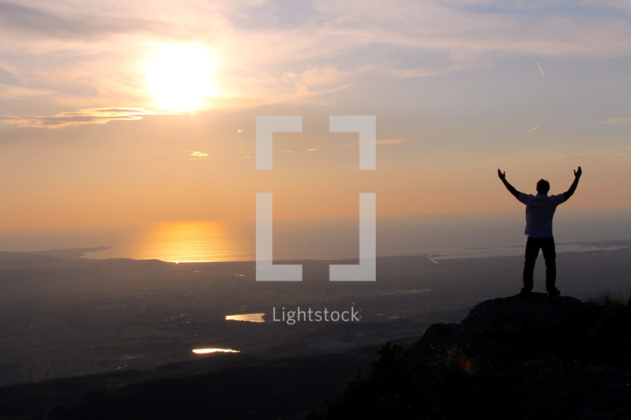 silhouette of a man standing on a mountain top with raised hands in surrender to God