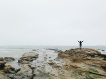 man with arms raised standing on a rocky shore