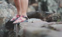 standing in sandals on a rocky ledge