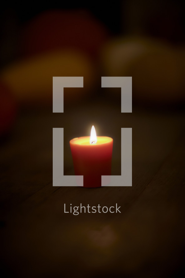 Lit candle on wooden table