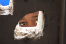 A child peeking through a hole in a wall.