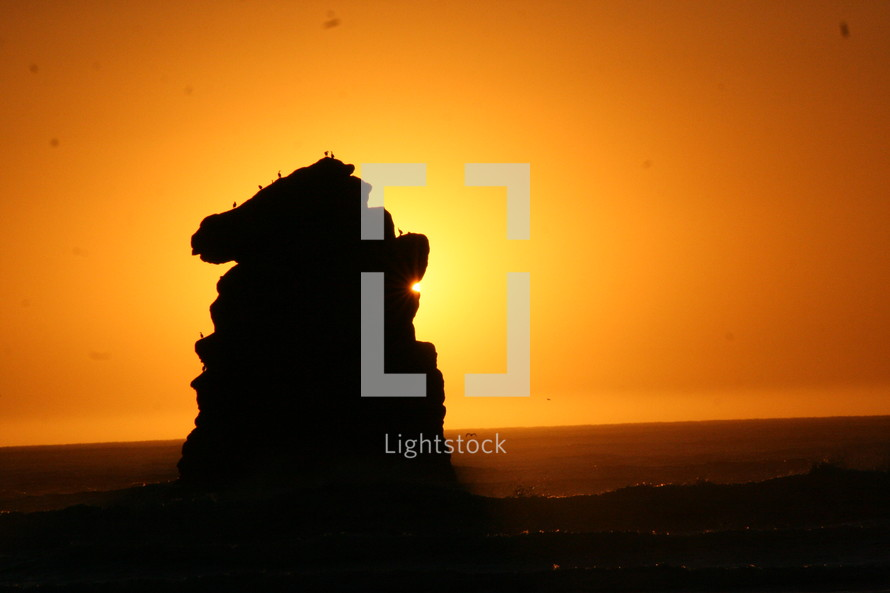 glowing sun behind a rock formation