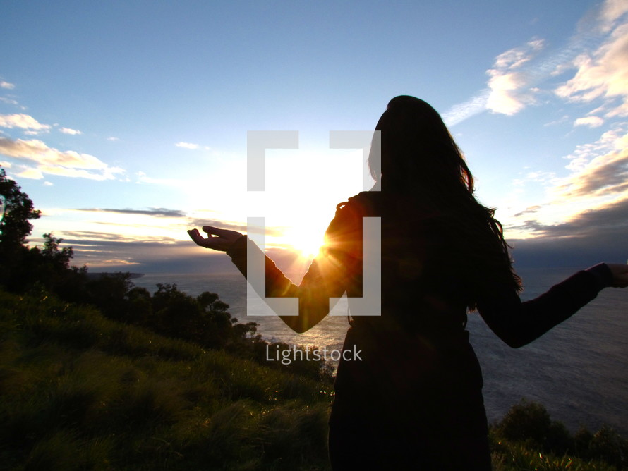 Silhouette of a woman appreciating the sunrise over the mountains.