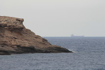 Marine coast with cargo ship on the horizon
