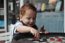 toddler boy playing checkers