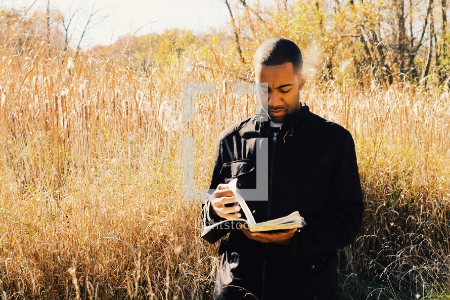 man reading a Bible in a field